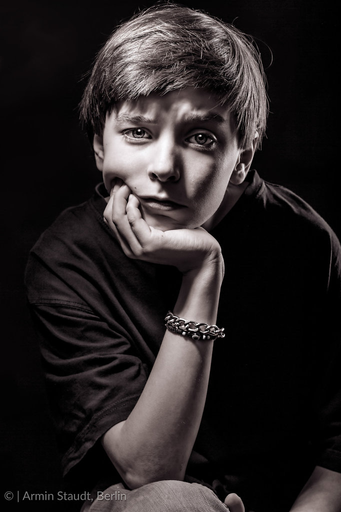 black and white portrait of a male teenager with black background