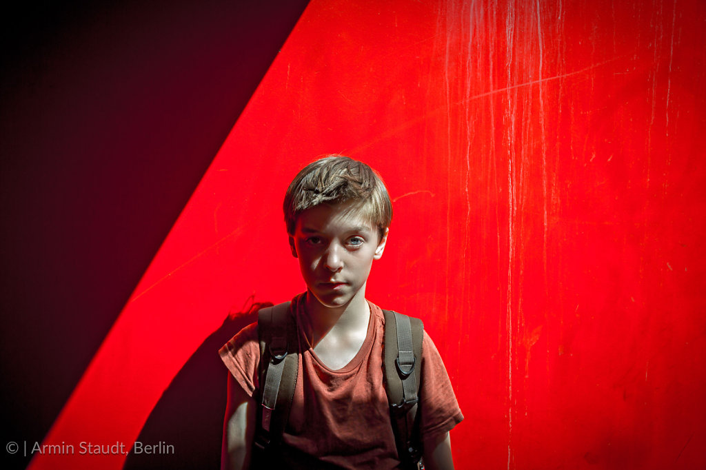 portrait of a teenager boy with rucksack in front of a red wall, with strong shadows