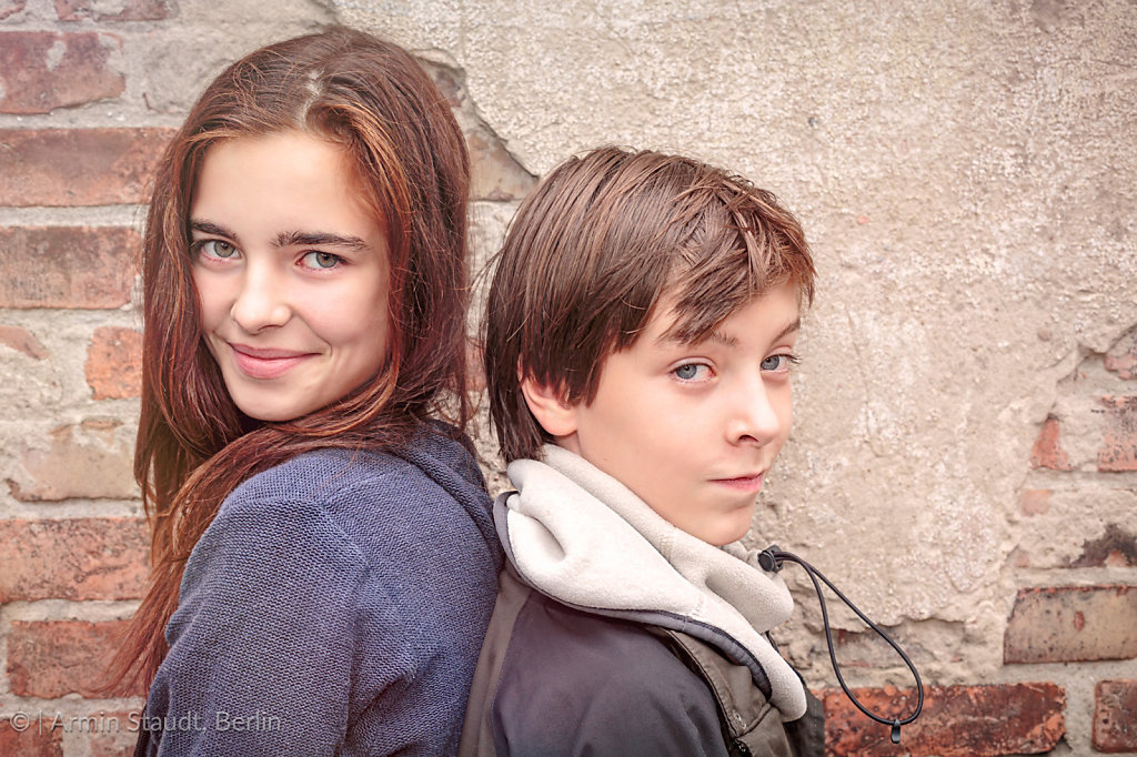 siblings back to back in front of an old brick wall