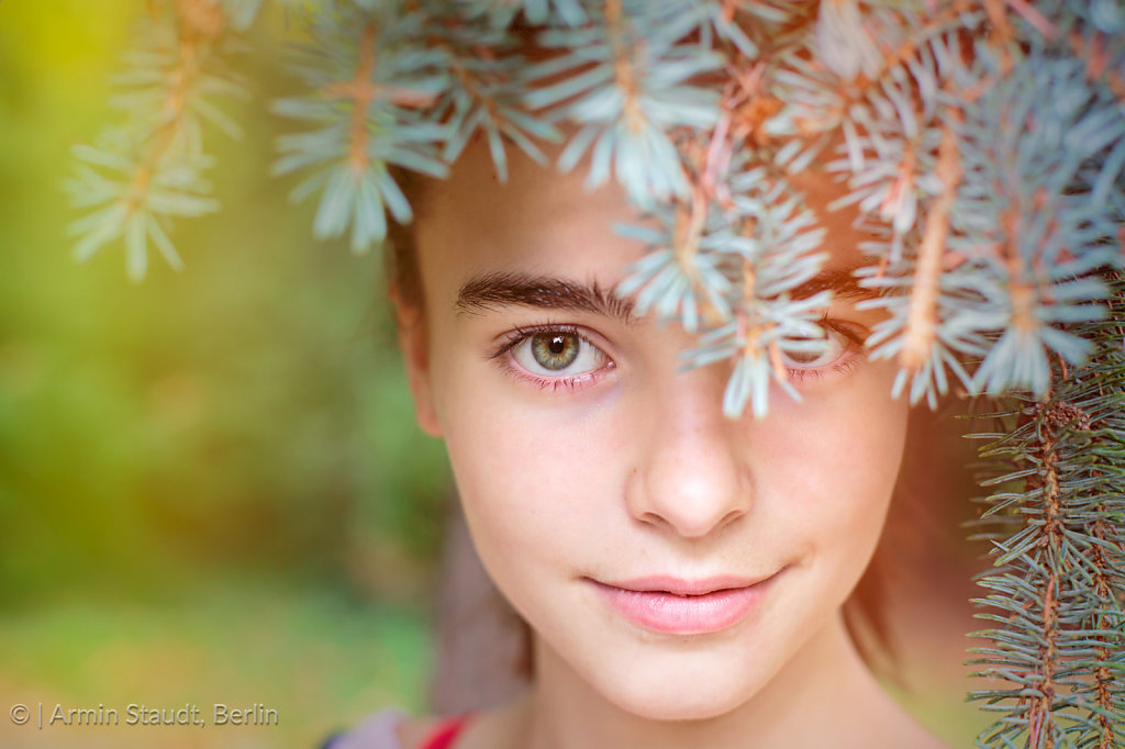 portrait of a smiling girl looking through blurred fir needles