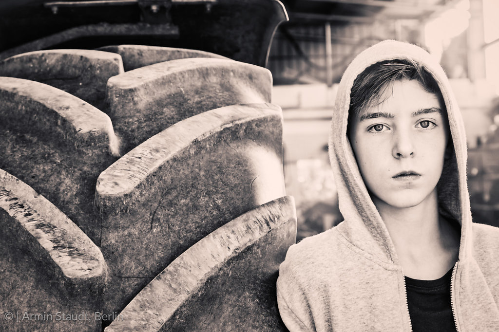 portrait of a teenage boy leaning against a huge tire