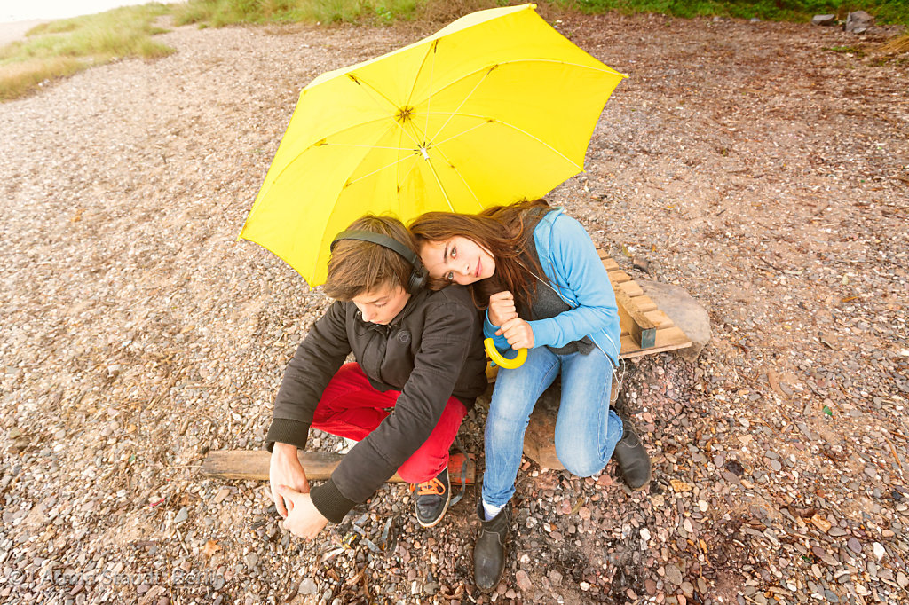 brother and sister with yellow umbrella sitting on a dirty beach