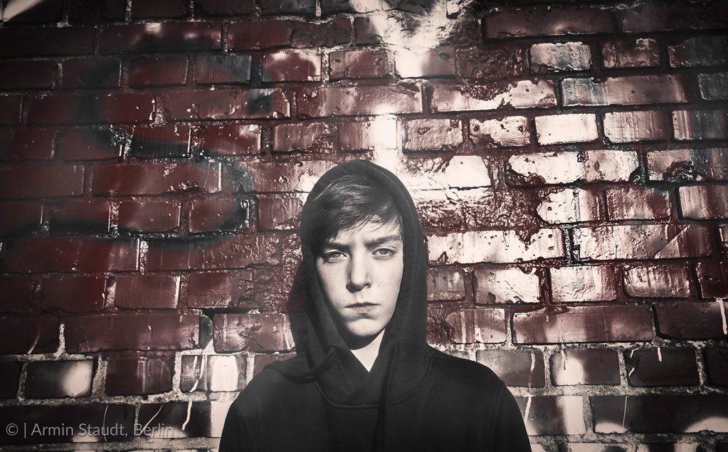portrait of a serious teenage boy in front of a red graffiti, vintage version