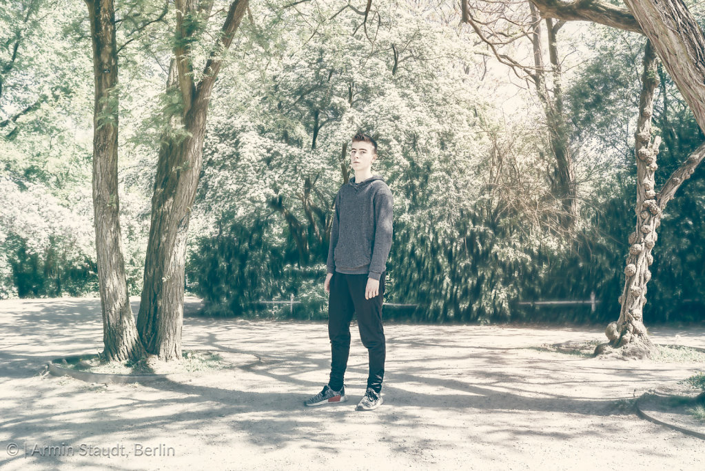 dreamy portrait of a standing young man in a park