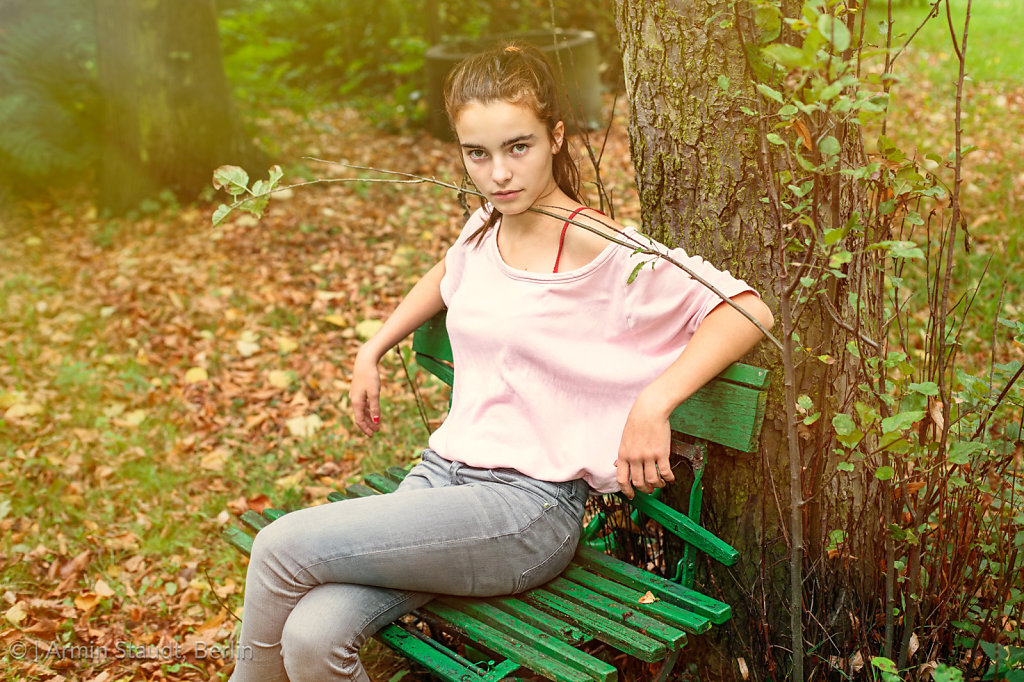 portrait of a strictly looking woman sitting on an old bench, to