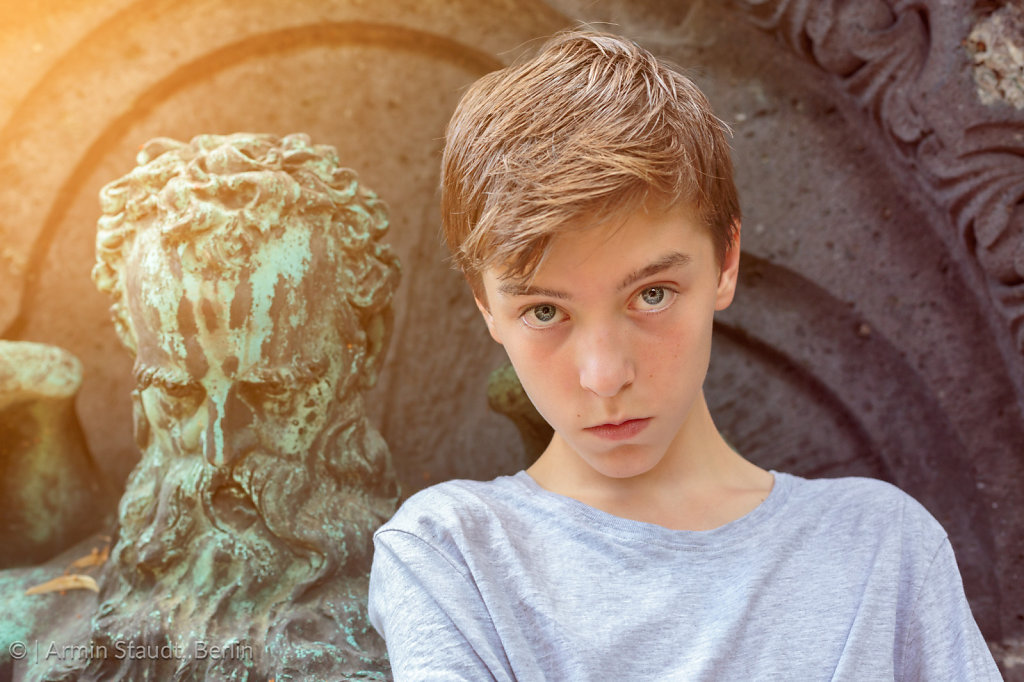 old and young, portrait of a teenage boy with sculpture of an ol