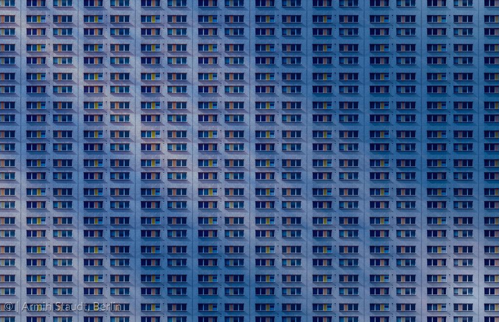 architectural pattern, dark concrete facade with mirroring sun