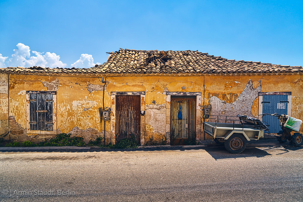 old yellow mediterranean cottage with blue sky