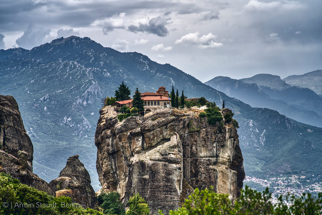 Monastery on a huge rock in Meteora, Greece with mountain range and dramatic clouds